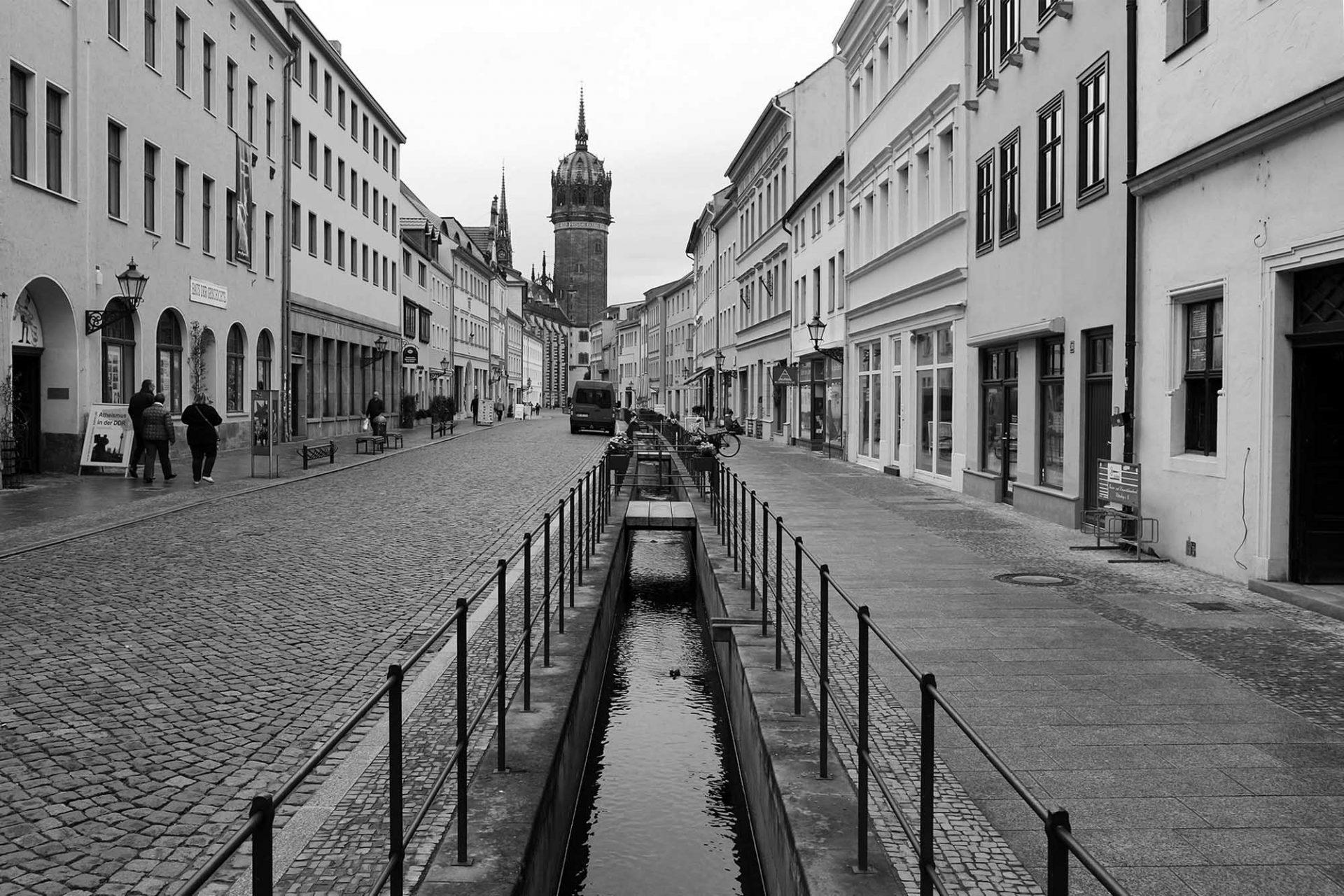 Stadtansichten. Es plätschert und rauscht. Die historischen Bäche wurden wieder offengelegt. Geranien begrünen deren Geländer.