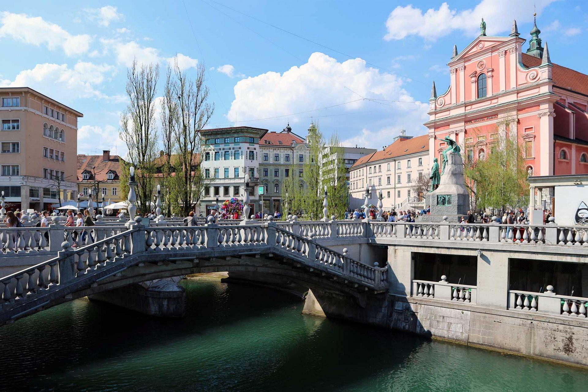 Dreibrücken. Das Brückenbauwerk wurde zwischen 1929 und 1932 errichtet. Der mittlere Teil basiert auf einer alten Steinbrücke aus dem 19. Jahrhundert. Plečnik fügte ihr zu jeder Seite zwei neue Brücken an, um den Prešerenplatz besser mit der Altstadt zu verbinden. Die Brücken selbst erhalten dadurch ihren besonderen Platzcharakter. Treppen führen zu beiden Seiten hinunter zu den Uferkanten. Plečnik hatte sich durch die Brückenbauten Venedigs inspirieren lassen. Zu allen Seiten eröffnen sich Ein-, Aus- und Durchblicke in die Stadt und auf den Strom.