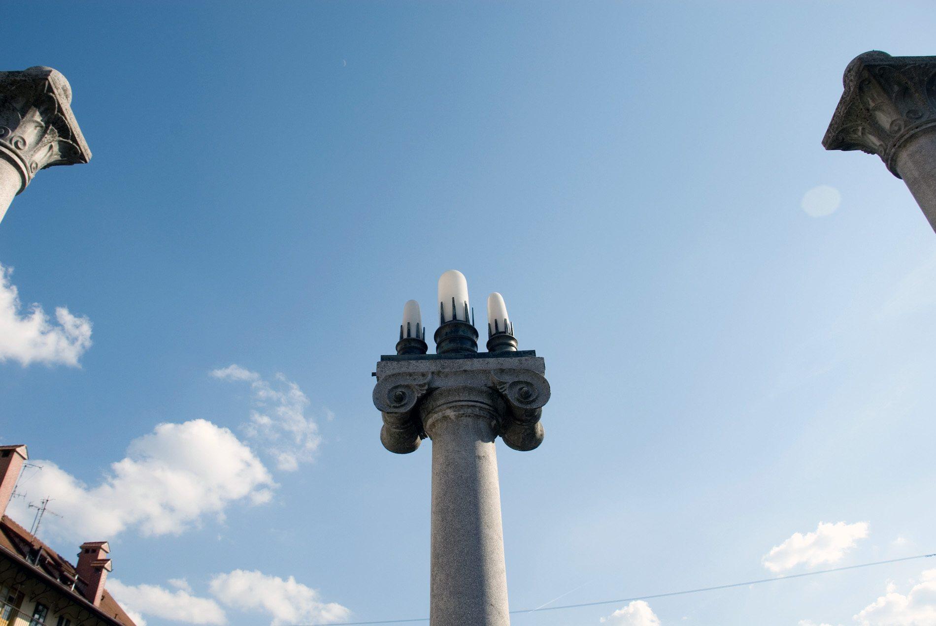 Schusterbrücke.  Etwas niedriger positionierte er zu beiden Seiten je eine Säule mit Volutenkapitellen, die von drei Leuchten gekrönt werden. Sie symbolisieren den Triglav, den höchsten Gipfel des Landes in den Julischen Alpen.