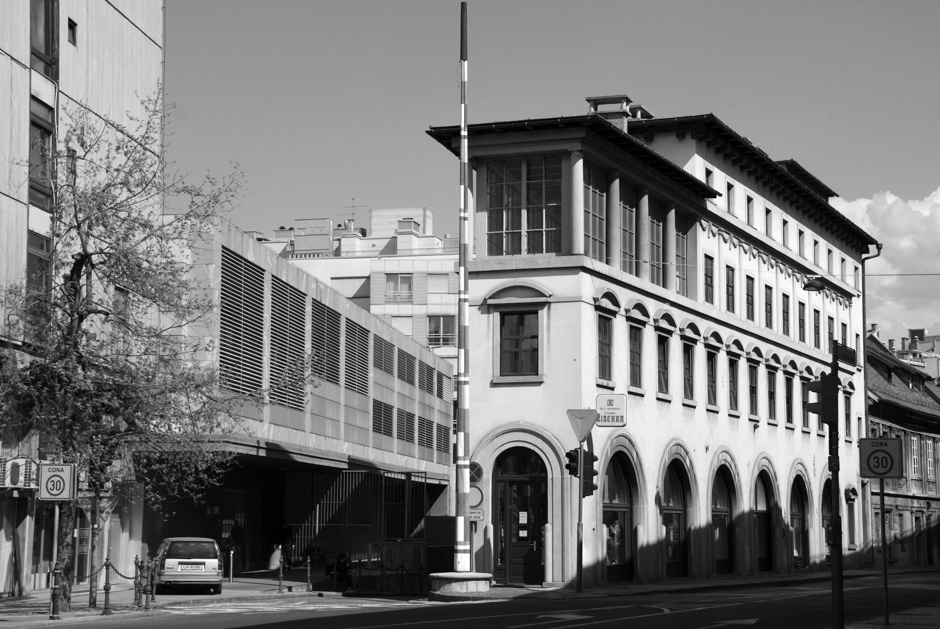 Bügeleisen.  Den Namen erhielt des Haus, errichtet zwischen 1933 und 1934, bereits durch einen Vorgängerbau. Es steht auf einem schmalen dreieckigen Grundstück unweit der Markthallen. Zur Poljanska Straße entwarf Plečnik eine mehrgeschossige Fassade mit großen Bogenfenstern im Erdgeschoss, von Halbbögen gekrönten Fenstern im ersten Geschoss und einer Reihe einfacher Fenster in der zweiten Etage. Besonders eindrucksvoll ist der säulenbegrenzte Wintergarten an der Spitze des Hauses.