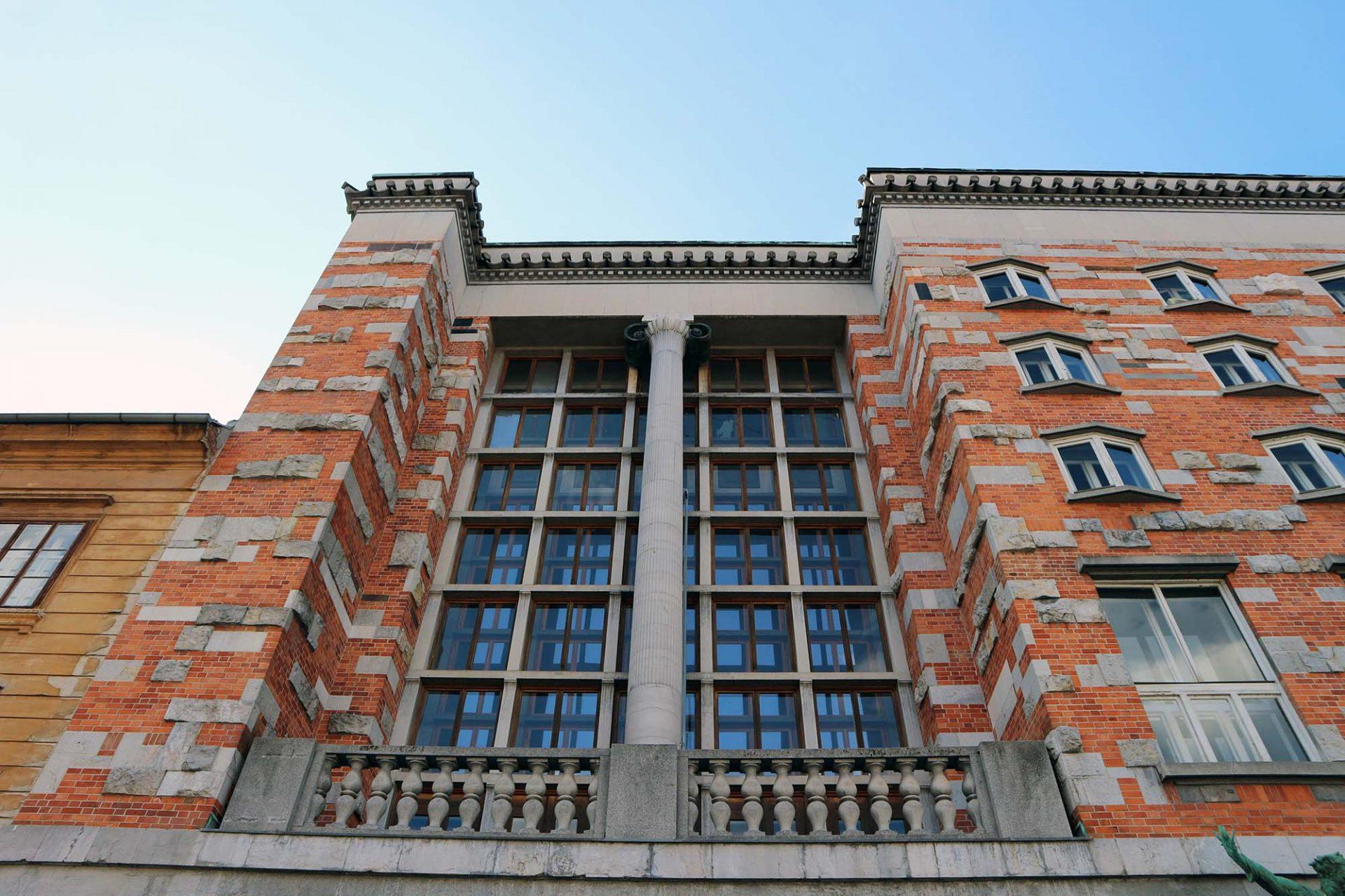 Nationalbibliothek. Ungewöhnlich sind auch die Oberflächen der Außenfassaden aus rotem Ziegelstein mit eingearbeiteten Steinen und Spolien aus römischer, mittelalterlicher und neuerer Zeit. Die Fenster erinnern an aufgeschlagene Bücher.