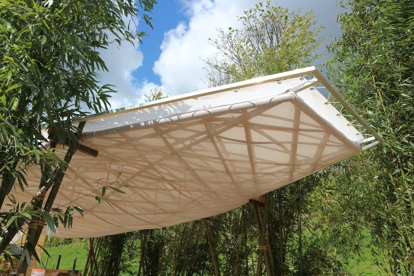 """Horizonte, Bambushain. Als schnellwachsendes Gras kann Bambus nach drei Jahren geerntet und genutzt werden. Die Ausstellung im Pavillon befasst sich mit Gebäuden und Objekten aus Bambus. Der Torre di Bambù entstand 2015 in Kooperation mit Bambuseto und weiteren Partnern und wurde auf der Ausstellung Green Utopia """"Green Utopia"""", einer Sonderschau der Möbelmesse, gezeigt."""