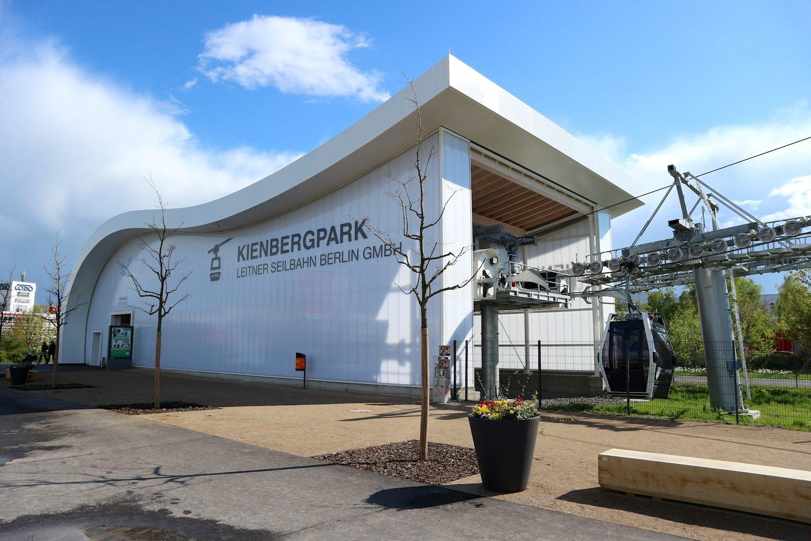 """Seilbahnstation.  Vom IGA-Haupteingang Kienbergpark am U-Bahnhof """"Kienberg - Gärten der Welt"""" (früher: """"Neue Grottkauer Straße"""") steigen die Kabinen mit jeweils maximal 10 Personen in eine Höhe von 25 bis 30 Metern."""