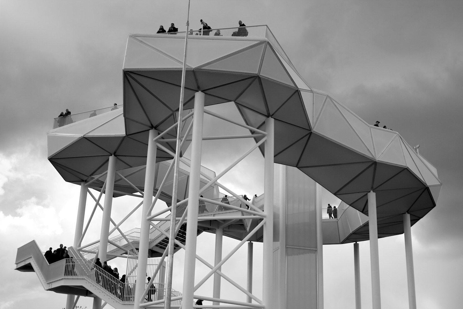 Wolkenhain.  Die aus einer transluzenten Membran bestehende Wolke ruht auf schlanken Stahlstützen, die unregelmäßig, wie die Stämme in einem Baumhain angeordnet sind.