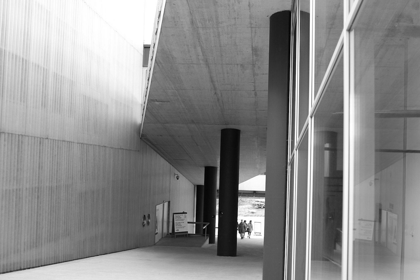 Kunsthal Rotterdam. Die Rampe führt vom Maasboulevard in Richtung Museumspark. Ein Schild weist Besucher*innen gen Eingang, anscheinend ist dieser schwer zu finden.