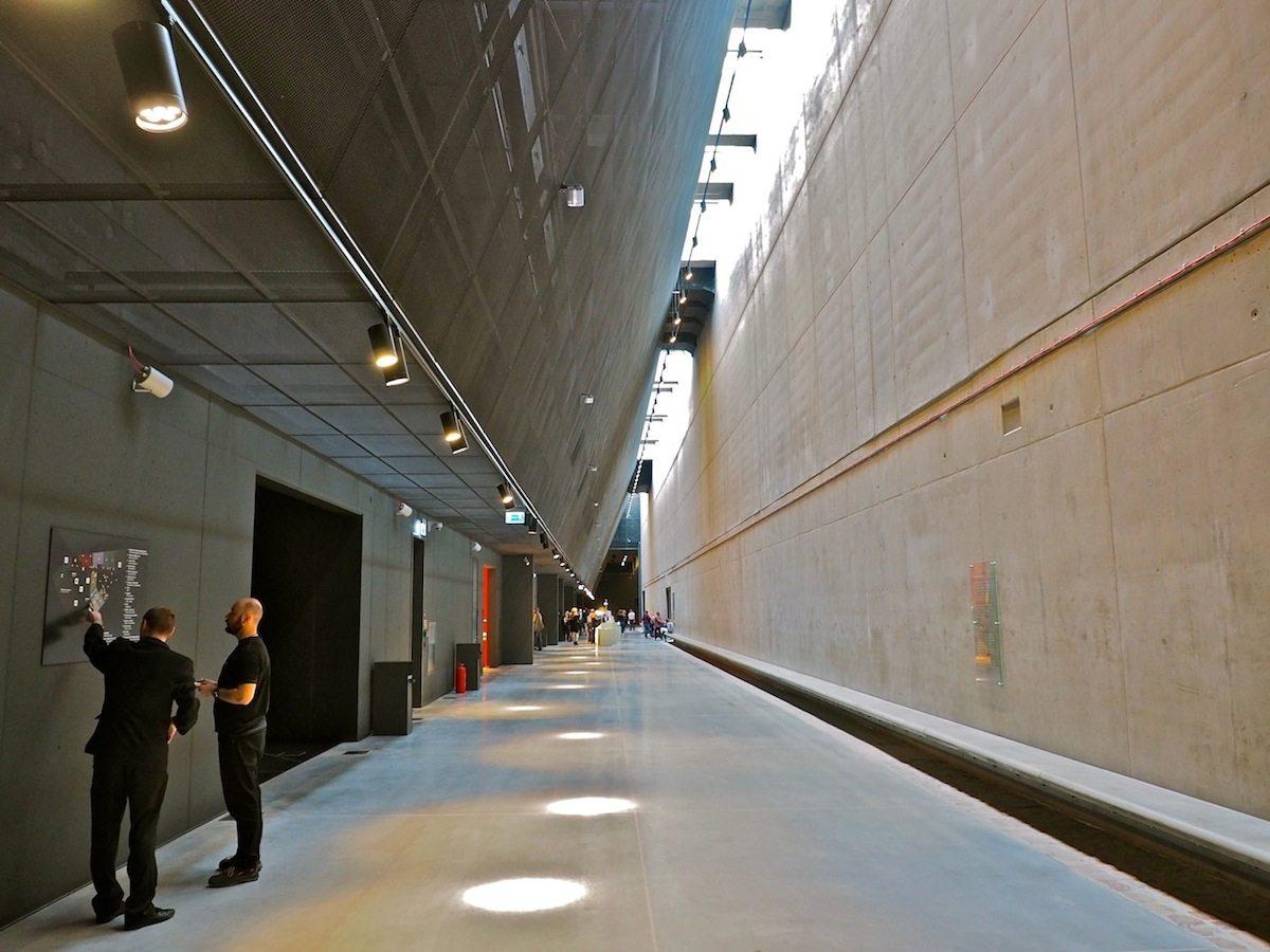Große Gasse..  Rechts und links der Hauptachse mit  ihren 122 Metern öffnen sich die Zugänge zu den achtzehn Räumen der Ausstellung. Die Passage verläuft entlang der Linie, der bis 1945 die Große Gasse in der nieder gebombten Altstadt folgte. Pflastersteine der Gasse sind unter der Sitzbank eingefügt.