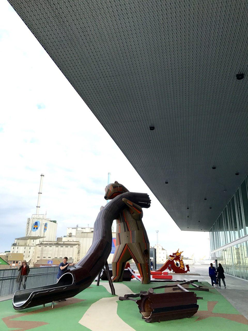 Dokk1. Für Kinderspaß ist draußen mit mehreren Themen-Spielplätzen gesorgt. Das Bild zeigt den kanadisch inspirierten Platz mit der Grizzly-Bär-Rutsche. Dahinter der Drache der chinesischen Spielfläche.