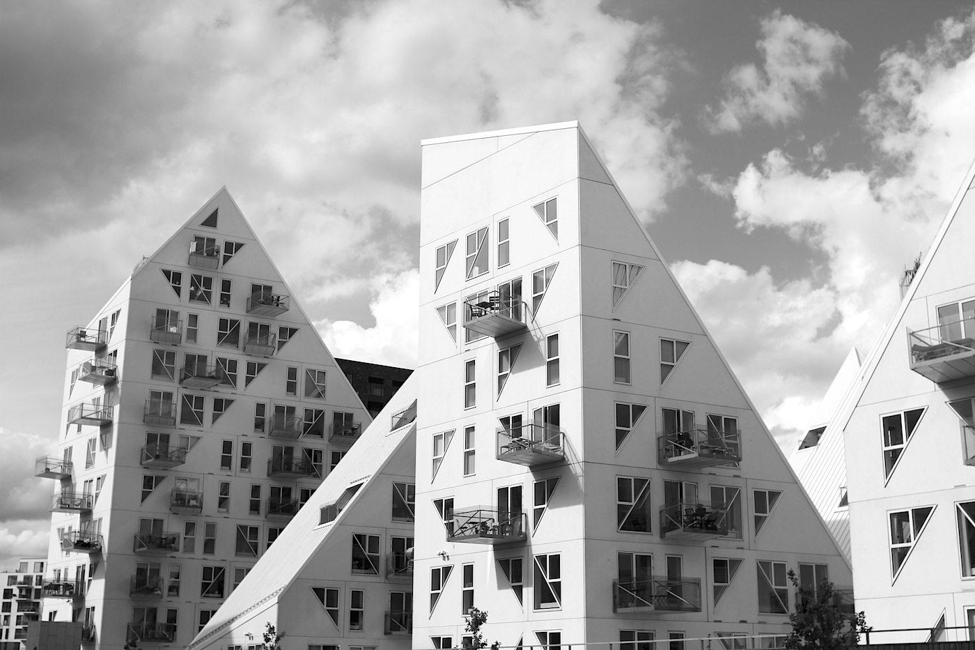 Der Eisberg. Die Stadt hat für ein Drittel der Wohnungen eine Mietpreisobergrenze festgelegt mit dem Ziel der sozialen Durchmischung. Die weiße Metalldeckung der großen Dachflächen ist mit Titandioxid beschichtet, die Schadstoffe aus der Luft filtern.