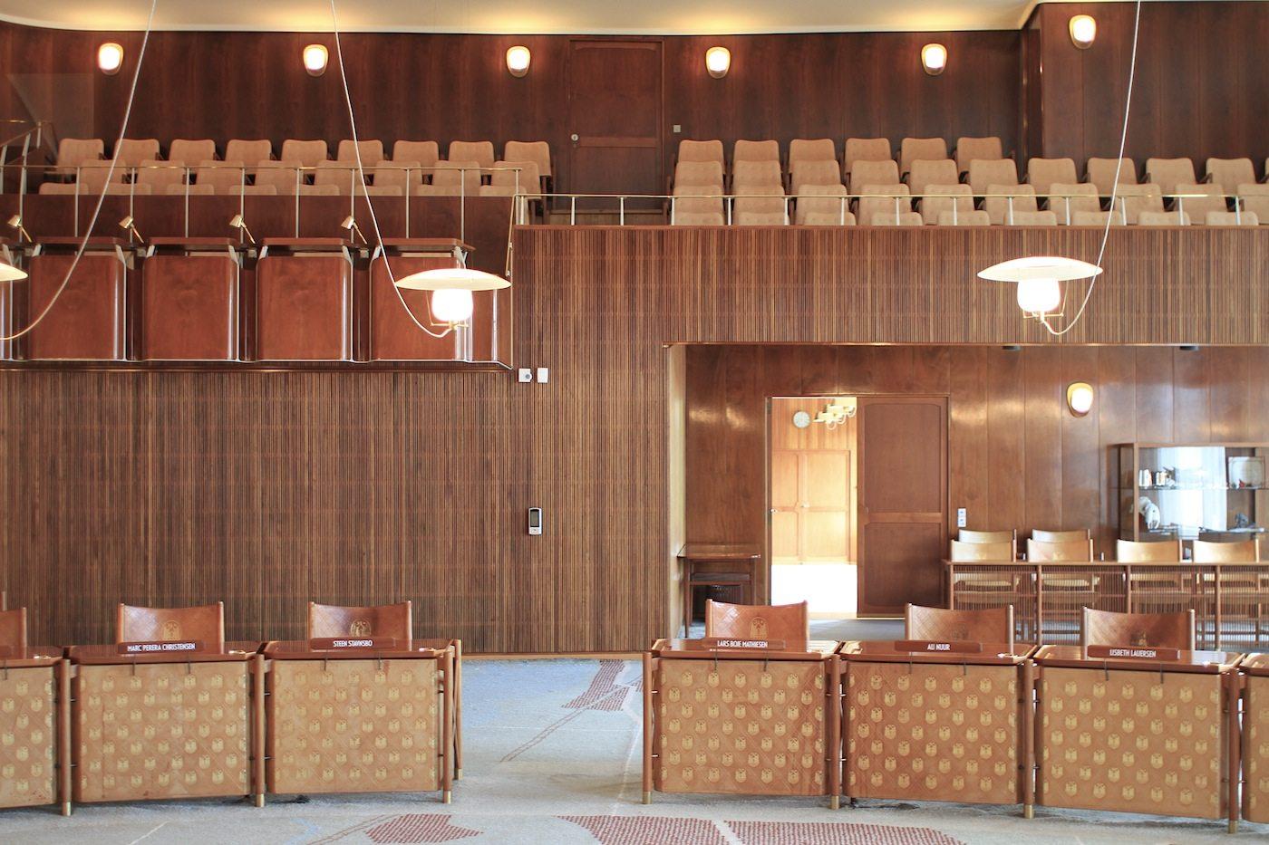 Die Öffentlichkeit.  Gegenüber dem Rund der Ratsmitglieder sind erhöht und links die Plätze für die Medienvertreter, dahinter die Sitze für Zuschauer.