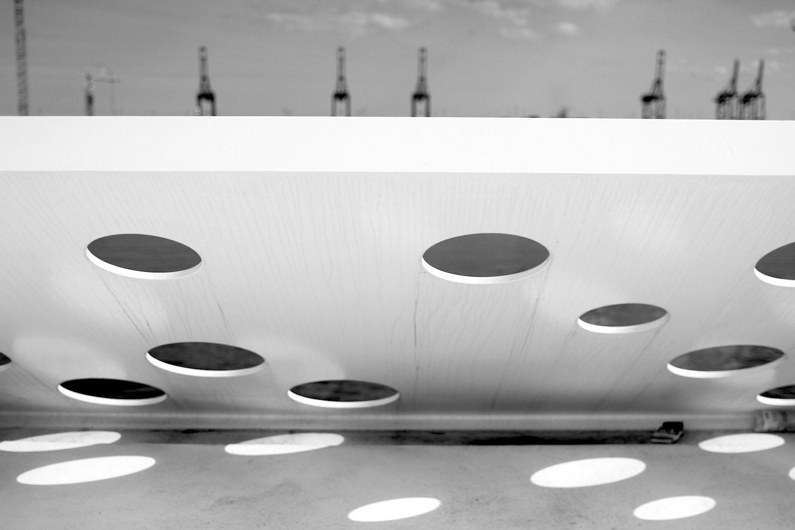 """The Salling Tower.  Kreisrunde Ausschnitte und Kanten: der Blick auf die Kräne des neuen Containerterminals. Dazu die Architektin: """"We always attempt to work with a material and try to see what it can do in relation to the sculptural or in relation to the place."""""""