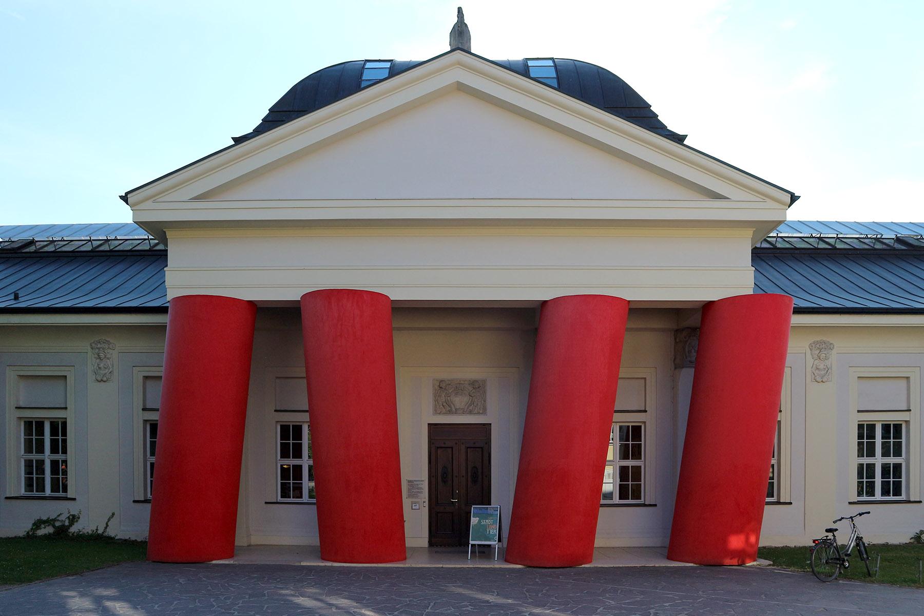 """Installation.  der tschechischen Künstlerin Magdalena Jetelová """"Venceremos/Sale"""" von 2006 prägt mit den vier roten Säulen das Eingangsportal des Museums."""