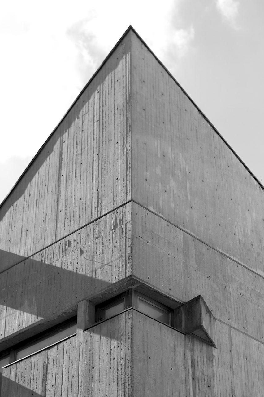 """Spitze.  """"Grundgedanke war ein mehrgeschossiges Magazin mit direktem Verkauf. Diese für die  damalige Zeit neuartige Idee wurde durch stützenfreie Räume, verbunden über ein frei im Raum stehendes Treppenelement, das den Kunden in das Obergeschoss führt, verwirklicht."""" –aus """"Regensburg Architektur"""", hg. von der Fachhochschule Regensburg."""