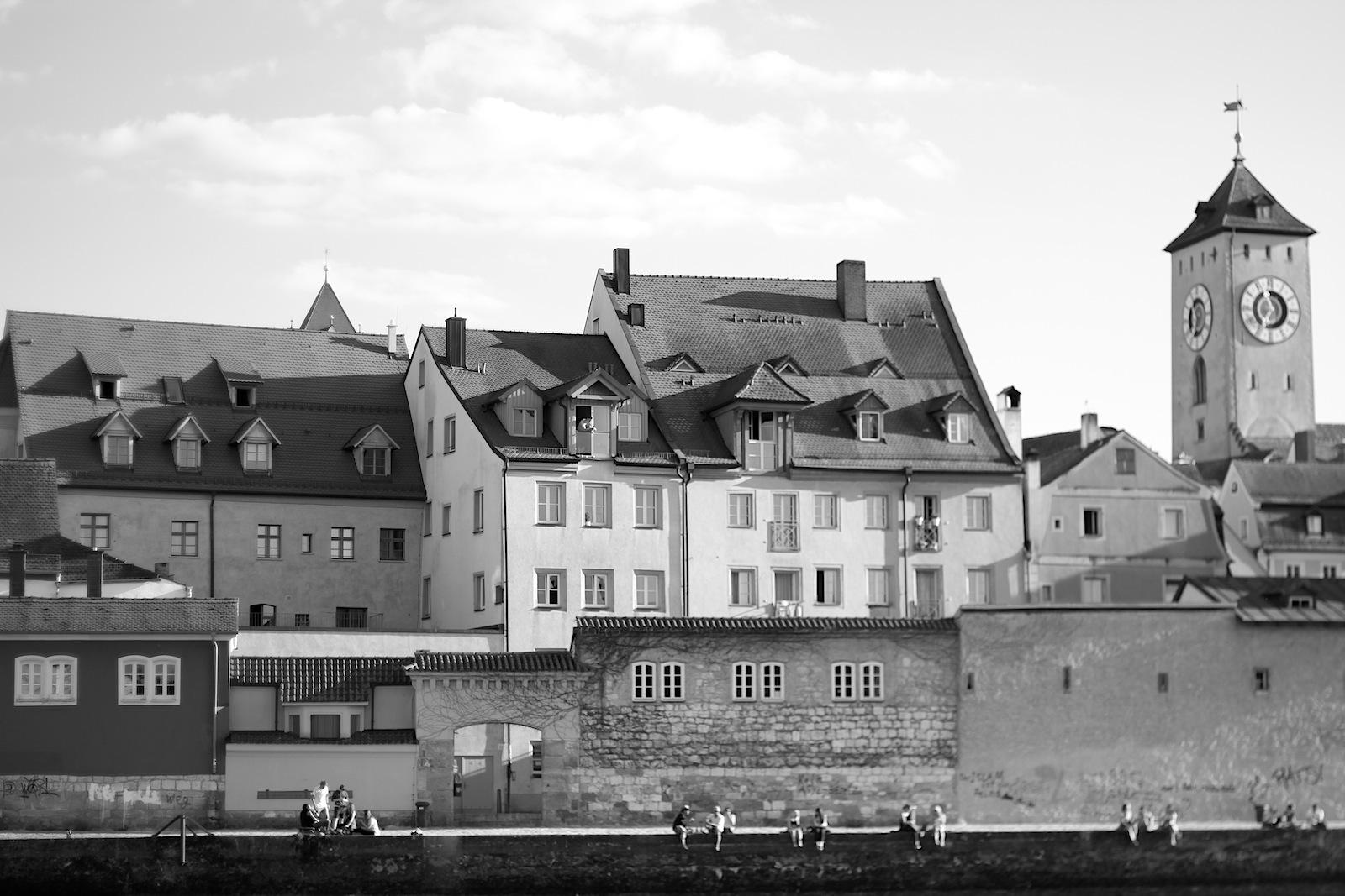 Blick. auf die Mittlere Altstadt mit dem, was man an Sonnentagen an der Uferkante macht: die Seele (und Beine baumeln) lassen.