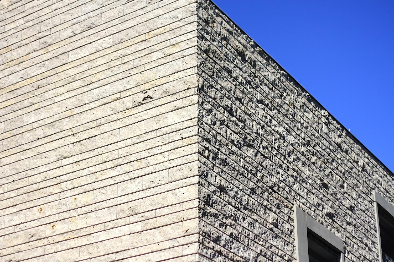 """Zitat.  """"Die gewollt robuste Oberfläche der Fassade zitiert vielfältige Beispiele aus dem Regensburger Stadtgebiet."""" –dp architekten"""