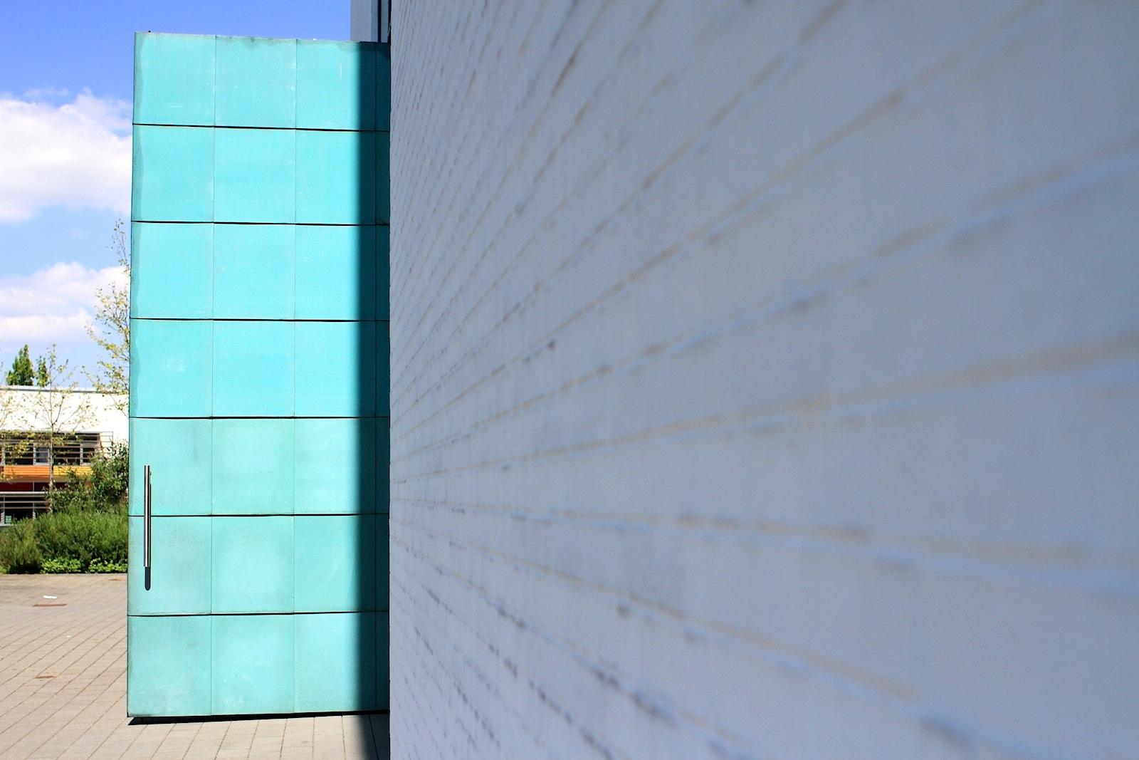 Offenheit.  Das Eingangsportal besteht aus einem mit Kupferblech belegten Drehflügel. Dieser, so die Planer, sollte ständig offen stehen.