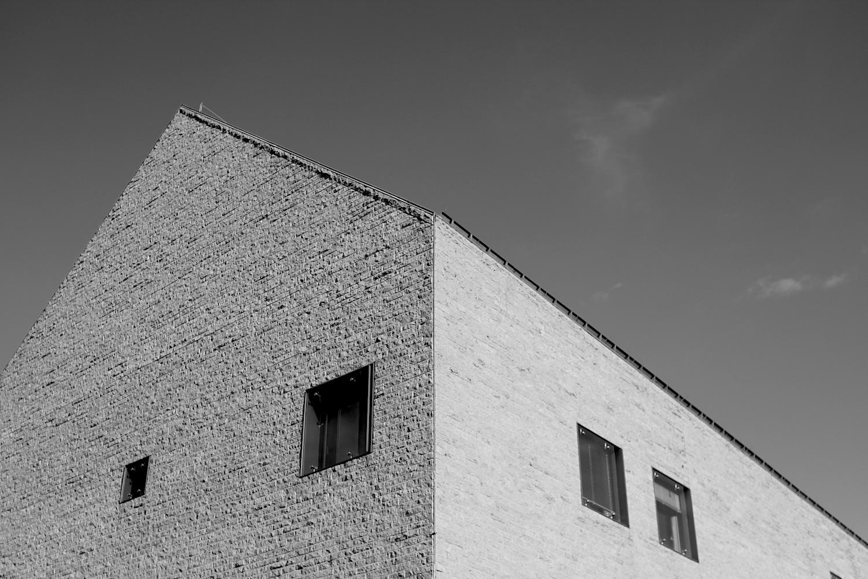 """Textilkaufhaus.  MGF Architekten GmbH Stuttgart konzipierte ein Kaufhaus in einer stark reduzierten Formsprache und dem klaren Natursteinmauerwerk. Das Gebäude erhielt 2004 den Bayerischen Bauherrenpreis in der Kategorie """"Stadterneuerung, vitale Innenstadt""""."""