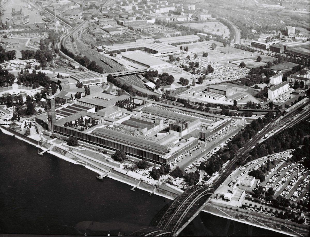 Um 1960. Luftaufnahme des Kölner Messegeländes mit Halle 10 und der neuen Sporthalle. Die Koelnmesse organisiert und betreut jedes Jahr rund 80 Messen, Ausstellungen, Gastveranstaltungen und Special Events in Köln und in den wichtigsten Märkten weltweit. Für mehr als 25 Branchen stellen diese Veranstaltungen die Weltleitmessen dar.