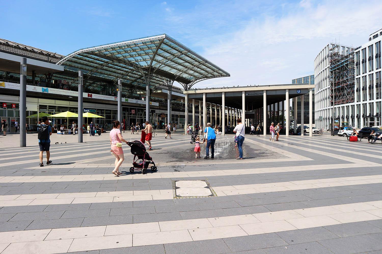 Breslauer Platz, Fertigstellung der Neugestaltung 2013. Gestaltung durch Büder + Menzel Architekten, Brühl / Köln. Der Breslauer Platz befindet sich auf der Nordostseite des Hauptbahnhofs. Die Umwandlung in einen Stadtraum hat einige Zeit in Anspruch genommen. Das Resultat der Arbeit von Kai Büder und Manfred Menzel ist mehr Übersichtlichkeit und ein klar gestalteter öffentlicher Raum mit mehr Platz für die Passanten. Unter jedem der drei säulengetragenen Pavillondächer des Bahnhofs entstand eine wettergeschützte Erweiterung der vorgelagerten Platzfläche als Eingänge zur Haltestelle und zum Hauptbahnhof.