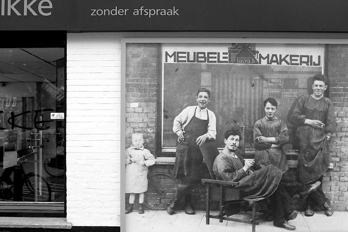 Werkstatt. Rietveld (im Lehnstuhl) und seine Mitarbeiter vor der Werkstatt in der Adriaen an Ostadelaan. Seit 1923 begann er seine Möbel zu bemalen. Berühmt wurde die rot-blaue Version dieses Stuhls.