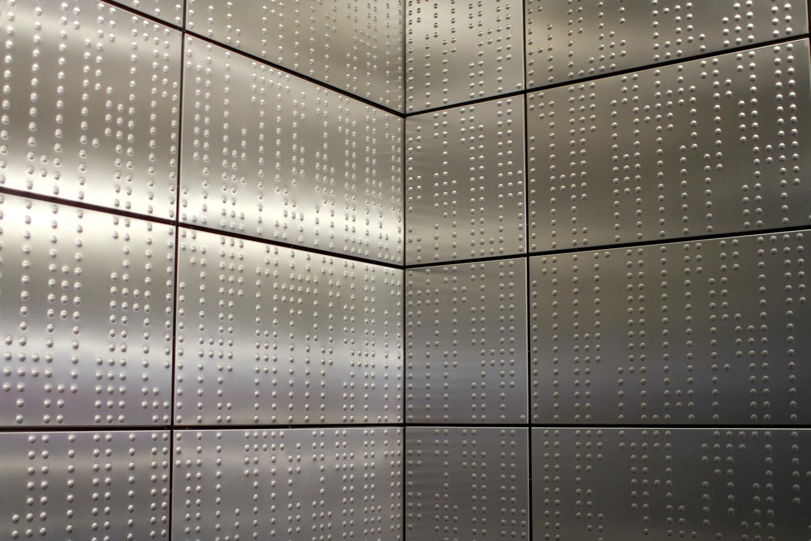 Station Benrather Straße.  Die Prägung der Wandverkleidung setzt sich aus vertikalen Punktreihen zusammen.