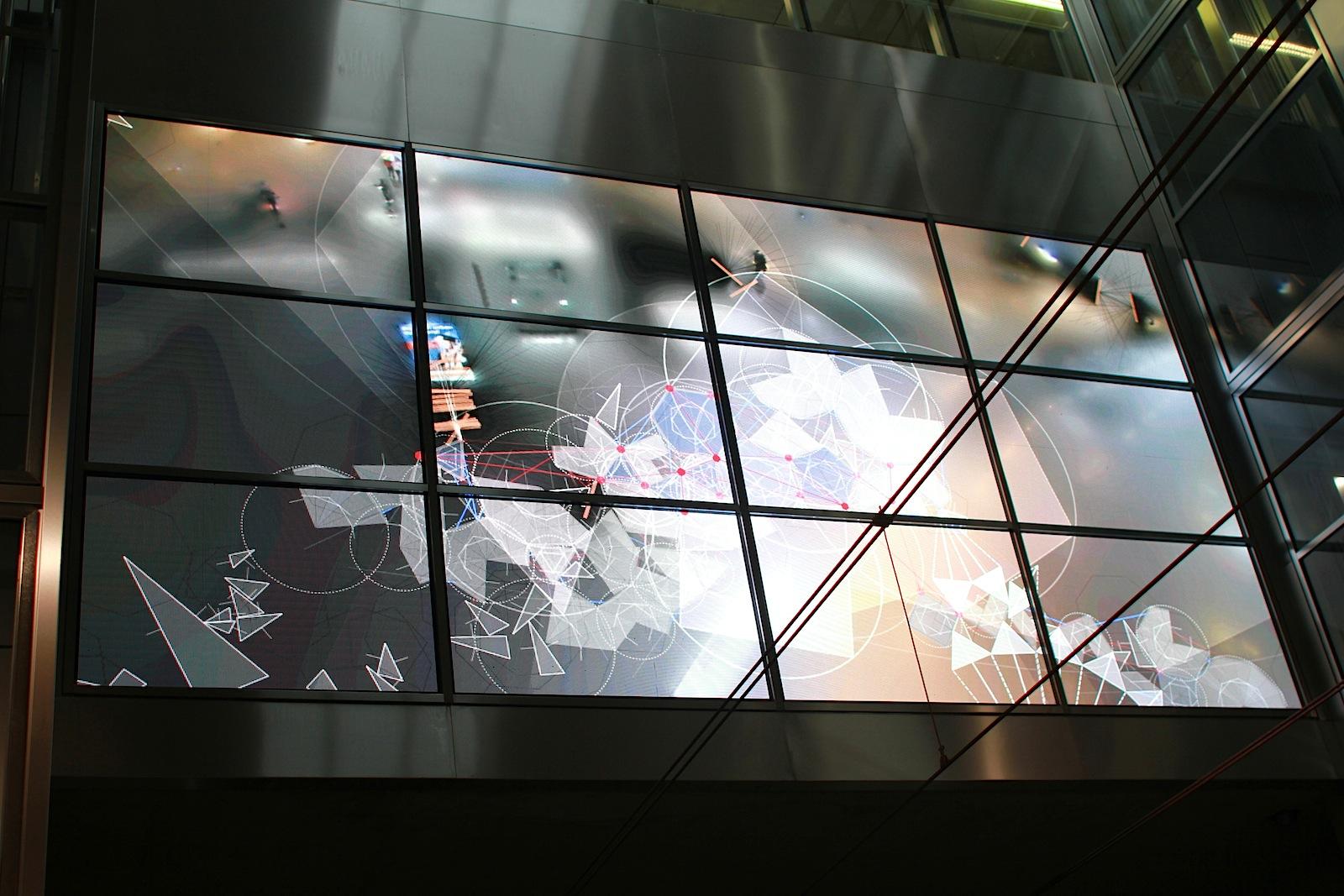 Station Schadowstraße.  Die zentrale Projektionsfläche ist in die große Stirnwand des Bahnhofs integriert, wo ein reaktives, digitale Video in Echtzeit generiert wird.