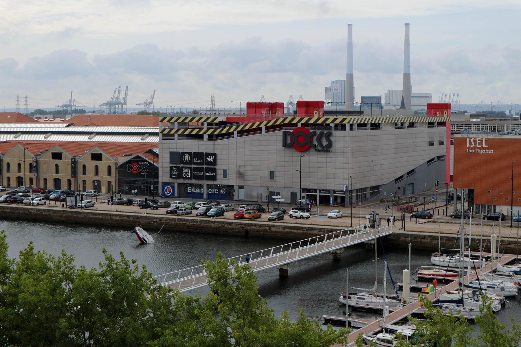 """Parcours Les Bassins. Im Südosten wurden 1846 nach Vorbild der Londoner Docks Lagerhallen für Kaffee, Gewürze und Baumwolle errichtet. Heute zählt das Quartier zu einem der größten Transformationsgebiete der Stadt mit Freizeit-, Wohn- und Gewerbebauten. Für den Sommer versenkte Julien Berthier ein Boot im Bassin Vauban, der Titel des Kunstwerks """"Love Love""""."""