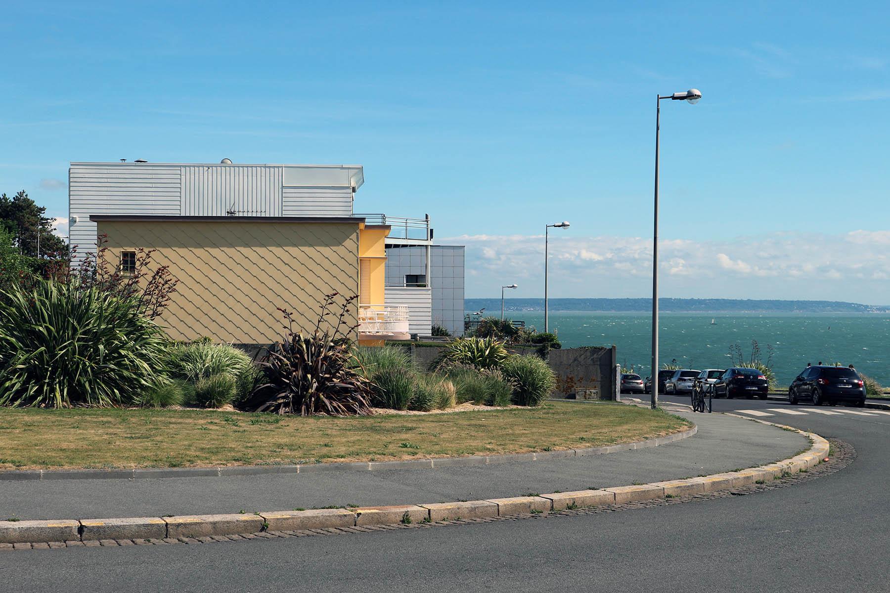 """Sainte-Adresse.  Schon vor Auguste Perret zog das Licht der Normandie Maler in seinen Bann. Im Jahre 1872 malte Claude Monet im Hafen von Le Havre ein Bild mit dem Titel Impression """"Soleil levant"""". Dieses Kunstwerk verhalf übrigens dem damals neuen Stil in der Malerei zu der Bezeichnung Impressionismus."""