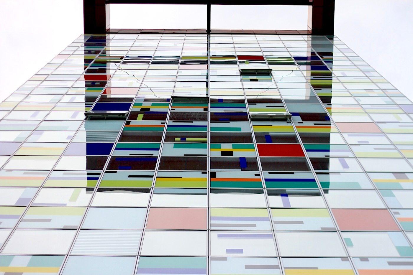 Colorium.  Von William Allen Alsop. Fertigstellung 2001. 17-geschossiges Hochhaus mit mehrfarbiger Fassade und rotem Technikgeschoss. Über 2200 farbig bedruckte Glaspaneele bilden mit einem innenliegenden Sonnenschutz die Vorhangfassade.