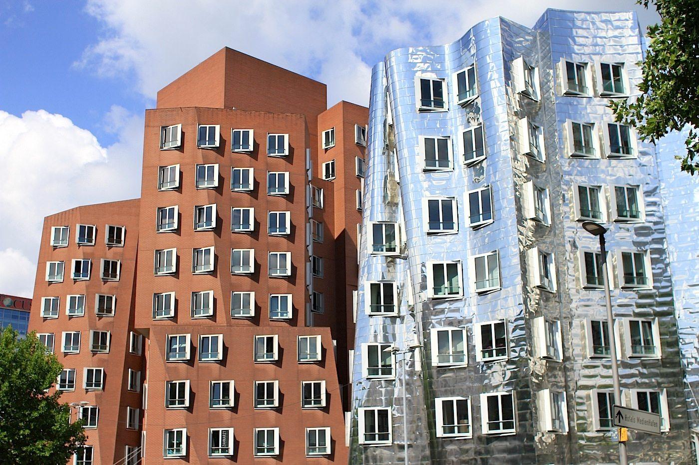 Neuer Zollhof 1–3.  Haus A: roter Klinker, Haus B: Edelstahl.