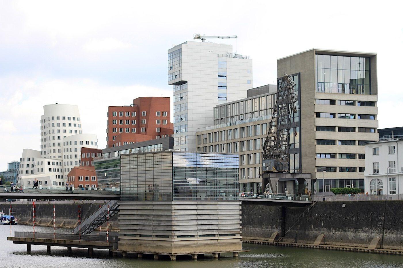 Am Handelshafen. Der Blick vom Julo-Levin-Ufer auf den Neuen Zollhof, den Chipperfield-Bau und die Fußgänger- und Radfahrerbrücke mit dem Pavillon (von slapa oberholz pszczulny sop architekten). Der Entwurf für den weißen hochaufragenden Turm stammt von Steven Holl.
