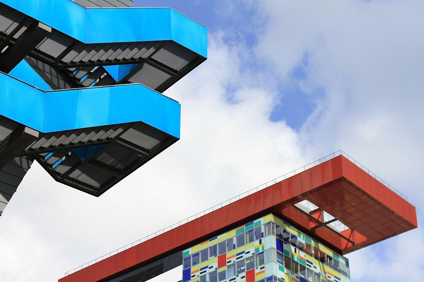 """Am Handelshafen 4.  PEC Port Event Center und DOCK – Düsseldorf  Office Center. Von Jo Coenen, Maastricht. Fertigstellung: 2002. Der """"Wolkenbügel"""" von Professor Wansleben, Köln. Fertigstellung: 2002. Rechts im Bild: das Colorium."""