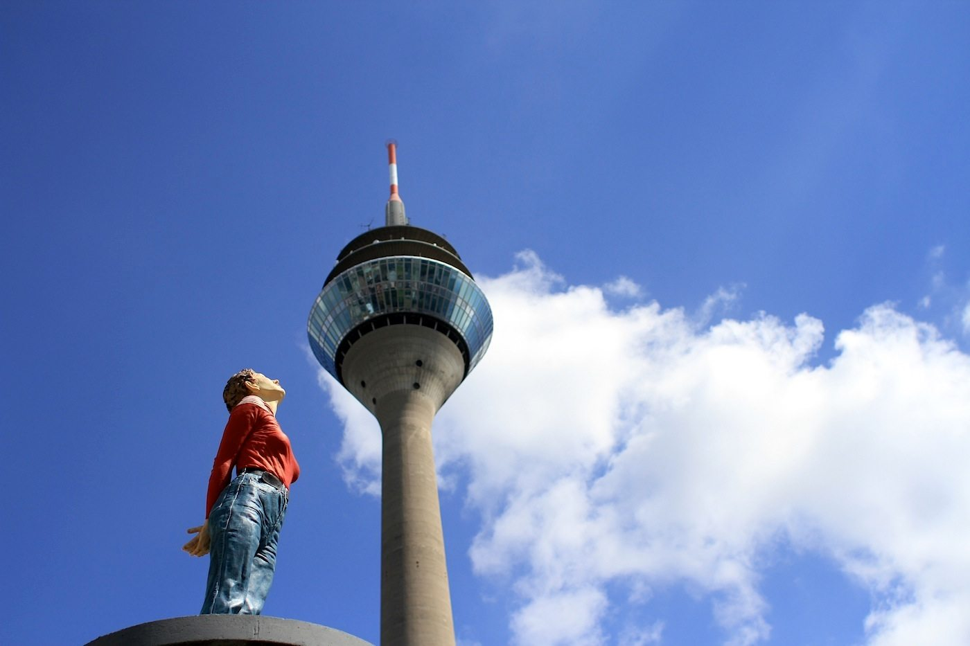 """Pillar saint """"Marlis"""" with the rhine tower.  TV tower by Harald Deilmann. Completion: 1982. Height: 234 m. """"Marlis"""" by Christoph Poggeler, who presented his """"pillar saint"""" since 2001 with sculptures of people on advertising pillars. Poggeler on the bases of advertising pillars puts children, couples, businessmen, holiday-makers or homeless - all in the Dusseldorf city centre. People from the middle of society - lifted out of the everyday life."""