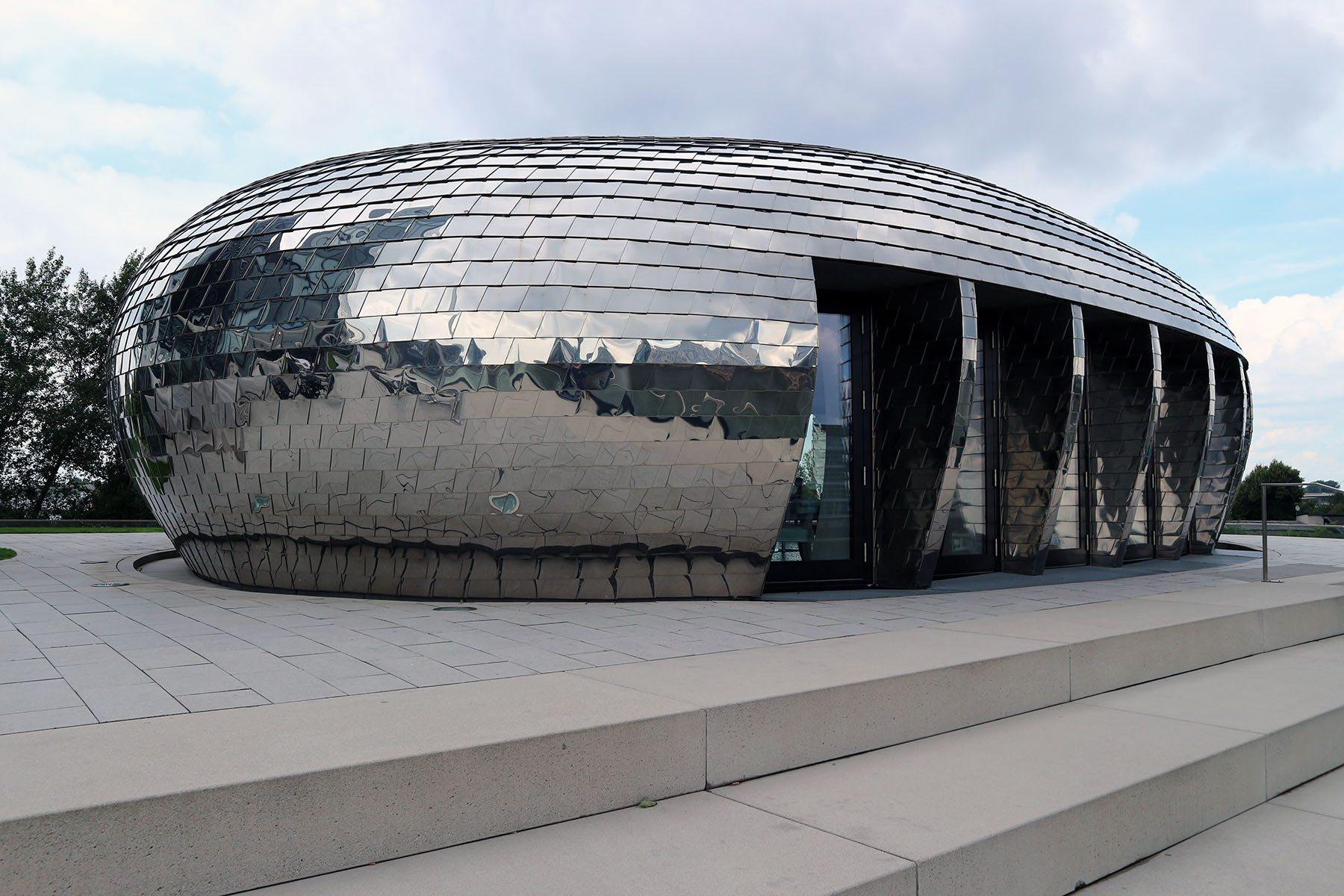 """Raumschiff.  Im ufo-ähnlichen und mit Aluschindeln verkleideten Pavillon (sop architekten) befindet sich die Lounge """"Pebble's"""". sop architekten sind auch für den entstehenden trivago campus verantwortlich."""