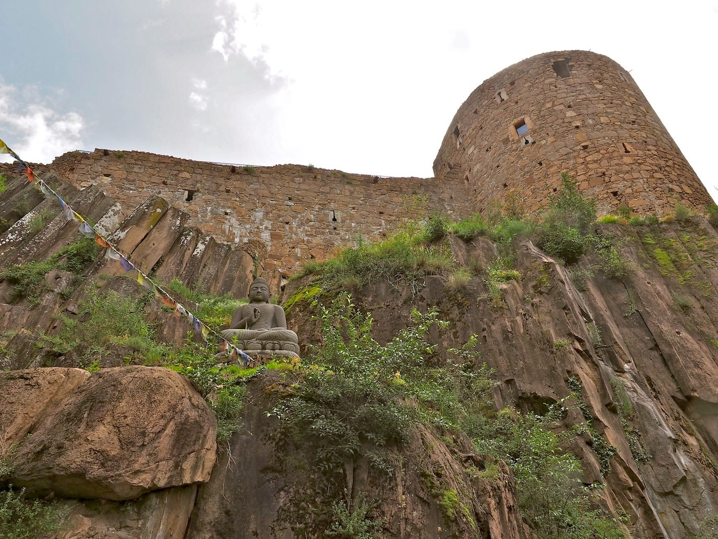 Buddha vor Burg.  Mit bis zu fünf Meter starken Mauern ließ Herzog Sigismund sein nach ihm benanntes Lieblingsschloss um 1475 schützen. Das weitläufige Gelände und die Türme der Festung auf dem Porphyrfelsen über Bozen bieten viel Platz für die Auswahl aus Reinhold Messners riesiger Sammlung.