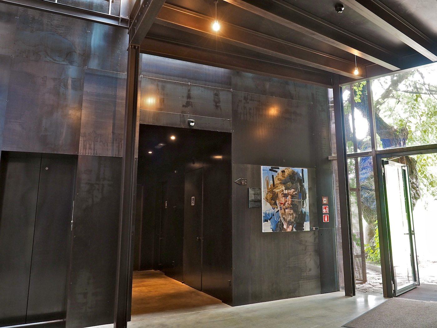 Einladung zur Kunst..  Erste Station auf dem weiten Rundkurs durch MMM Firmian ist ein Haus für Bilder, die ansonsten thematisch verteilt in fünf Türmen zu sehen sind. Nur Schrauben halten den Bau aus Stahl und Glas zusammen.