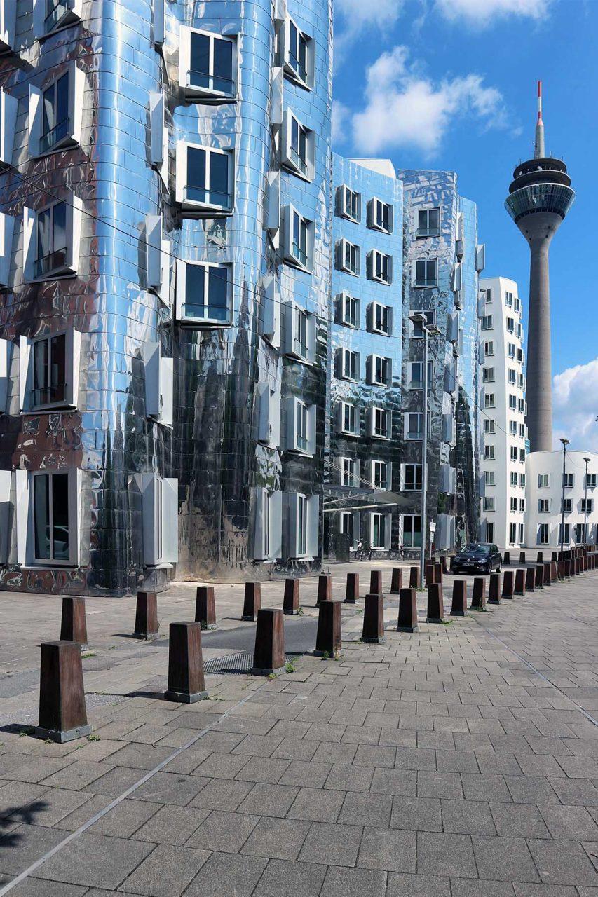 Neuer Zollhof 1–3.  Die Asymmetrie der Freiformflächen war zur Zeit der Planungen mit herkömmlichen Bauzeichnungen nicht darstellbar, so dass ein dreidimensionales Computerprogramm eingesetzt wurde. Damals eine Premiere in der Baubranche.