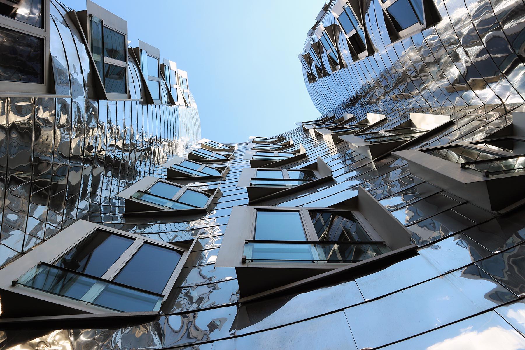 """Neuer Zollhof 1–3.  The developer, """"Kunst- und Medienzentrum Rheinhafen GmbH"""", commissioned the Dusseldorf-based """"BM+P-Architekten und Stadtplaner Beucker Maschlanka und Partner"""" and """"Philipp Holzmann Bauprojekt AG Niederlassung Dusseldorf"""" with the execution of Gehry's designs."""