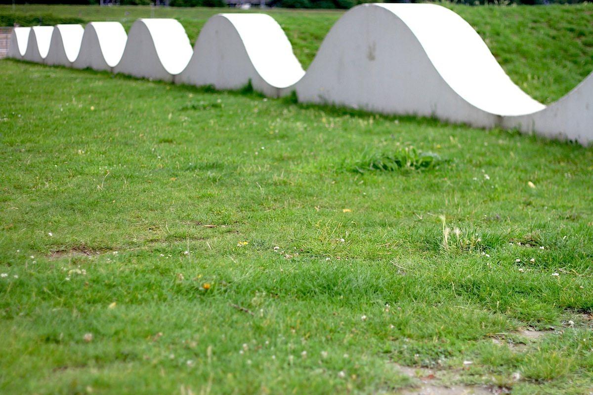 Garten der Erinnerung. Weiße Betonwellen fassen die Rasenwellen vor dem Hafenbecken.