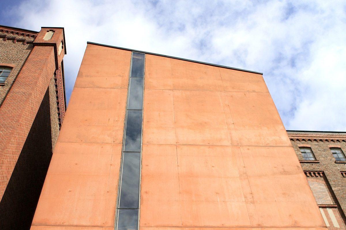 MKM Museum Küppersmühle.  Das renommierte Architekturbüro Herzog & de Meuron aus Basel, Schweiz, hat den Umbauplan entworfen, der sich durch einen maßvollen Umgang mit der Bausubstanz auszeichnet. An die Südfassade des Backsteinspeichers fügten sie ein neues Treppenhaus aus rotem Sichtbeton. Die Dachneigung führt einen Teil des Hauptgebäudes visuell fort. Ein vertikaler Fensterschlitz durchzieht die schlichte Form. Die Oberflächen sind innen und außen ziegelrot eingefärbt. Nur wenige Decken wurden herausgenommen, um den raumgreifenden Bildern neuer deutscher Maler wie Immendorff oder Penck die entsprechende Höhe zu ermöglichen. So entstand ein dreigeschossiges Ausstellungsgebäude. Zum Teil wurden Fenster vermauert, während an anderer Stelle lange vertikale Fensterbänder in die Ziegelfassade eingeschnitten wurden. Die Innenräume sind schlicht und ganz auf die Kunst ausgelegt mit wenig Ablenkung.