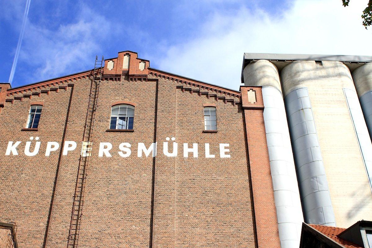 """MKM Museum Küppersmühle.  Entwurf Küppersmühle Gebrüder Kiefer und Joseph Weiß, Fertigstellung 1916. Umbau durch Herzog & de Meuron, Fertigstellung 1999. 1860 gründete der Unternehmer Wilhelm Vedder auf dem Areal des heutigen Museums Küppersmühle einen Mühlenbetrieb. Auf diese Weise förderte er die Entwicklung des Duisburger Innenhafens zum """"Brotkorb des Ruhrgebiets"""". 1969 fusionierte man mit den Homberger Küpperswerken, die der Mühle und dem Museum ihren Namen gaben. Das Backsteingebäude wurde wie die benachbarten Mühlen- und Speicherbauten saniert und 1999 als Museum Küppersmühle eröffnet. Es beherbergt auf 5.000 Quadratmeter Ausstellungsfläche die Sammlung des Duisburgers Hans Grote."""