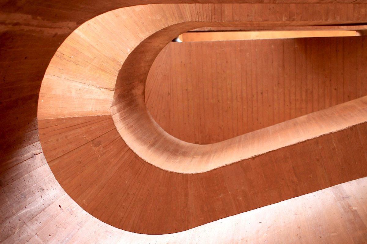 MKM Museum Küppersmühle.  Die einläufig gewendelte Betontreppe ist mit der Brüstung in einem Guss ausgeführt. Die Führungslinie verläuft um ein ovales Treppenauge in sanften Schleifen.