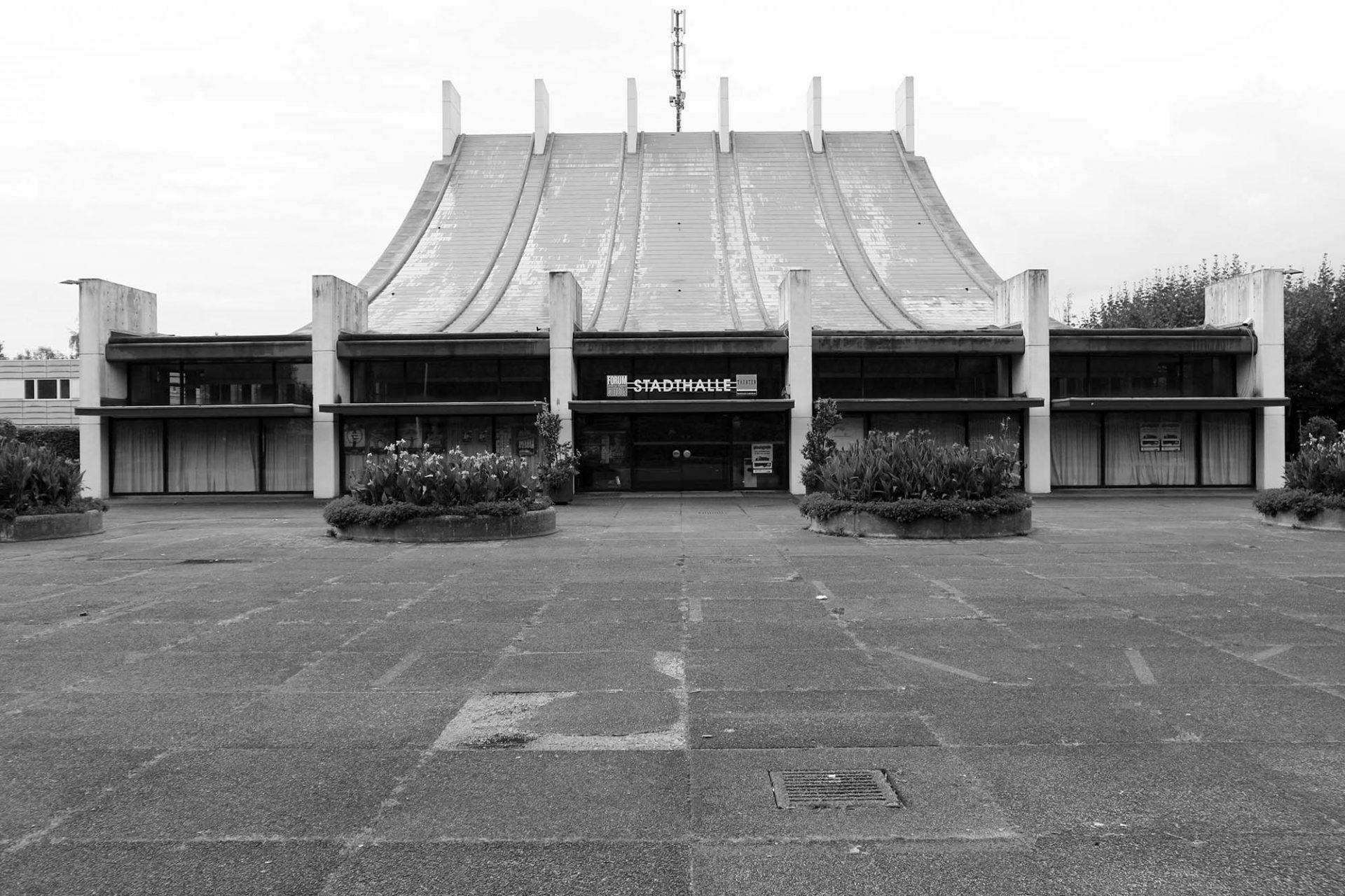 Stadthalle. Die Haupteingänge der Veranstaltungshallen sind zum Platz hin ausgerichtet. Deren Dächer schwingen hinab auf menschliches Maß.