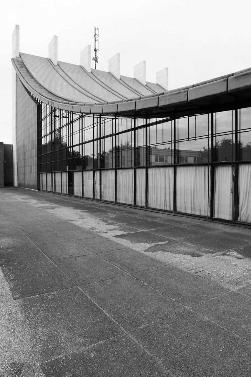Stadthalle. Die seitlichen Fassaden sind vollständig verglast mit feinen Rahmungen und Riegeln. Der dahinterliegende Sicht- und Sonnenschutz aus blauem Stoff ist größtenteils noch im Original erhalten.