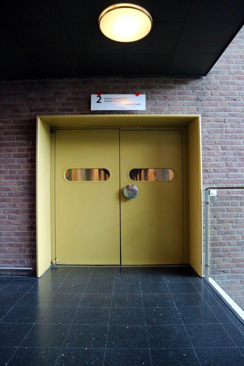 Rathaus Castrop-Rauxel. Beinahe alle Materialien und Farbgebungen sind noch im Original erhalten: dunkler Natursteinbelag, verglaste Brüstungen und farbige Türen entsprechend der verschiedenen Geschosse und Behörden.