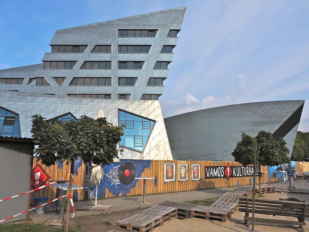 Kulturelle Konkurrenz. Die Vamos-Kulturhalle in einem industriellen Zweckbau bietet den Studenten Platz für Parties. Im sanft gebogenen Libeskind-Auditorium dahinter liegt die Messlatte etwas höher.