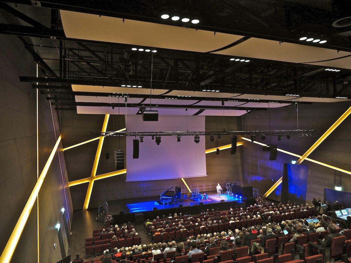 Farbenzauber. Die LED-Lichtlinien der Akustikbänder in den Wänden des Auditoriums können das gesamte Farbenspektrum durchspielen, um die zum Anlass passende Stimmung zu erzeugen.