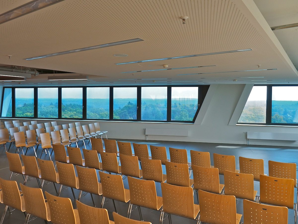 Raum für Seminare. Die mit Argon gefüllten Dreischeibenfenster verdunkeln sich bei Sonneneinfall selbst. Sie sind von Hand zu öffnen, CO2-Ampeln helfen bei effizientem Lüften. Das hilft beim sorgsamen Umgang mit Energie, dem auch die Wärmerückgewinnung und Versorgung aus Niedertemperatur-Abwärme dienen.