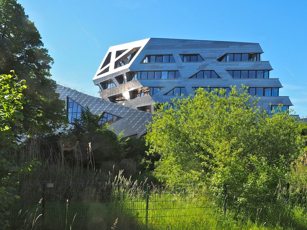 Loggia zur Stadt. Im Obergeschoss des Forschungszentrums erlaubt eine Plattform unter der von schrägen Stützen durchkreuzten Gebäudekante die freie Aussicht über den Biotopgarten bis nach Lüneburg.