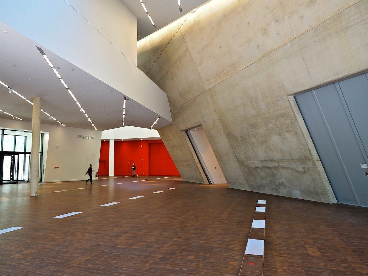 Rot, weiß, grau, braun. Wie hier im Foyer mit Blick zum Haupteingang ziehen sich vier Farben durch das gesamte Gebäude. Rot und weiß für Trennwände und Decken, grau für die tragenden Betonteile und braun für das Stabparkett im Erdgeschoss, dazu der dunkle Estrich für die Fußböden der oberen Stockwerke.