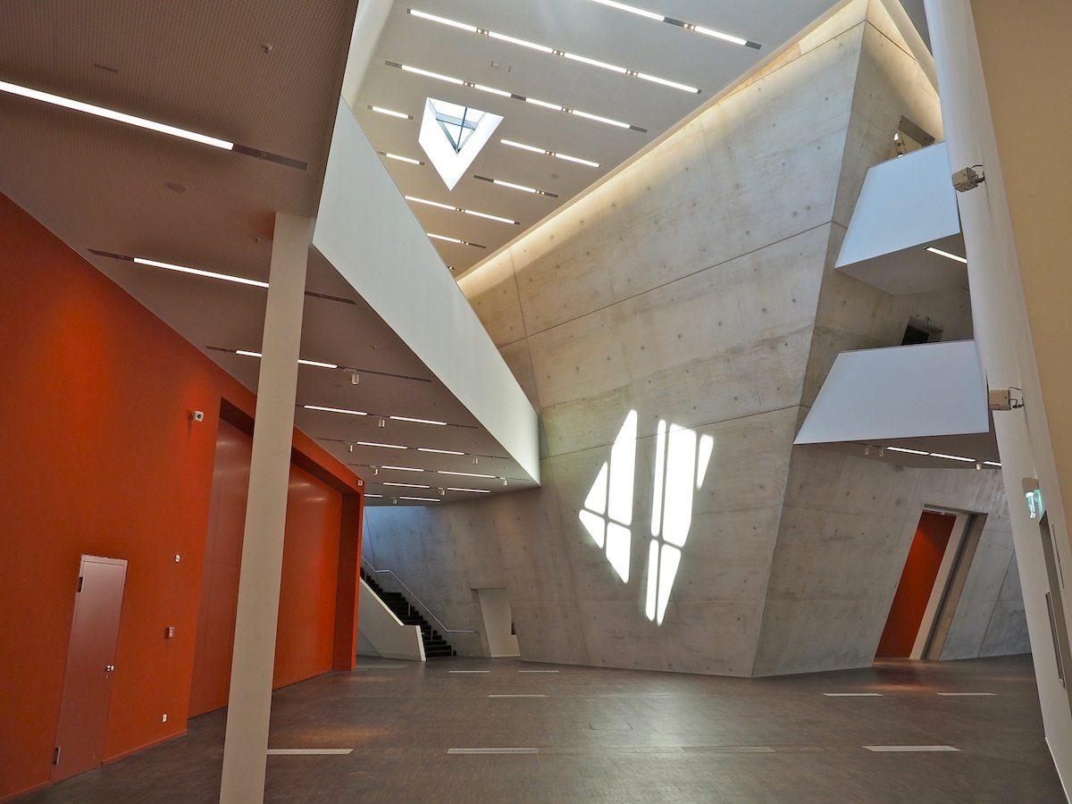 Vor dem Audimax. Lichthöfe mit einer Höhe bis zu 17 Metern füllen das Foyer mit Tageslicht. Durch die rote Pforte lässt es sich mit dem Libeskind-Auditorium verbinden.